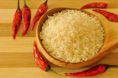 Breve riso crudo sul cucchiaio di legno con alcuni peperoncini rossi Fotografia Stock Libera da Diritti