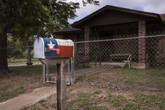 Brevlådan målade med Texas Flag i fron av ett hus i Texas, USA Arkivfoton