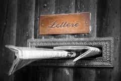 Brevlådatidning som sätts in in i den wood dörröppningen, gammalt byggnadshus (Italien) Fotografering för Bildbyråer