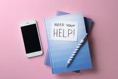 Brevpapper anmärkning BEHÖVER DIN HJÄLP och smartphone på färgbakgrund, bästa sikt arkivfoton