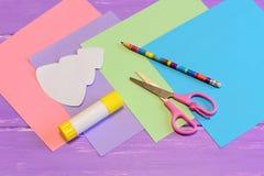 Brevpapper som skapar ett julhälsningkort från kulört papper Sax limpinne, blyertspenna, färgade pappersstycken Arkivbild