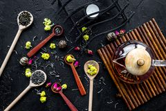 Brew the aromatic tea. Tea pot near wooden spoons with dried tea leaves, flowers and spices on black wooden background Stock Photo
