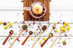 Brew the aromatic tea. Tea pot near wooden spoons with dried tea leaves, flowers and spices on white wooden background Stock Photos