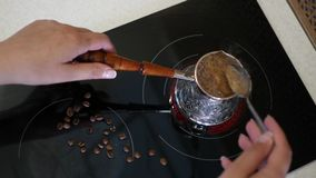 Brew coffee in a special Turkish on an electric stove, stirring with a spoon. 4k, 3840x2160. HD stock video footage