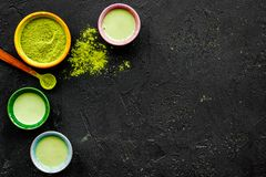 Brew matcha tea. Bowl with powder and cups with beverage on black background top view copy space. Brew matcha tea. Bowl with powder and cups with beverage on Royalty Free Stock Images