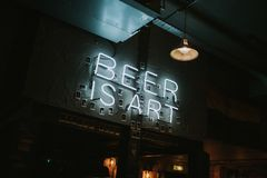 "Brewdog pub indoors decoration in Brighton, United Kingdom. BRIGHTON, ENGLAND - October 26th, 2018: A ""Beer is Art` neon lettering lights in a wall at stock image"