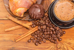 Brewed coffee, coffee beans, cinnamon sticks, chocolate truffle Royalty Free Stock Images