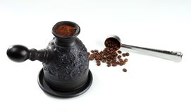 Brewed coffee with foam in a coffeepot. Freshly brewed coffee with foam in a coffeepot of black clay and a steel measuring spoon with fried coffee beans. On Royalty Free Stock Photo