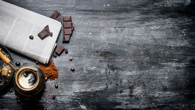 Brewed coffee pot with fresh newspaper and bitter chocolate. Stock Images