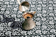 Brewed coffee on the tablecloth with ornaments Royalty Free Stock Photo
