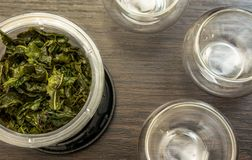 Brewed tea leaves. Brewed green tea leaves and cups royalty free stock photos