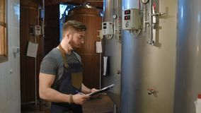 The brewer on the background of beer tanks makes calculations