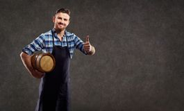 A brewer with a barrel in his hand. stock images