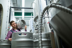 Brewer carrying keg. At brewery factory Stock Image