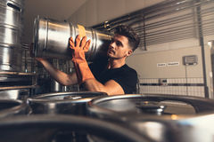 Brewer carrying metal beer barrel at brewery factory Royalty Free Stock Photos