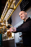 Brewer filling beer in beer glass from beer pump. Portrait of smiling brewer filling beer in beer glass from beer pump in bar Royalty Free Stock Photo