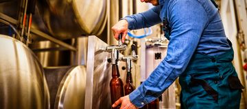 Brewer filling beer in bottle. From tank at brewery royalty free stock photo