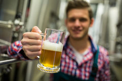 Brewer holding a glass of pint beer. Close-up of brewer holding a glass of pint beer royalty free stock photos