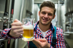 Brewer holding a glass of pint beer stock image