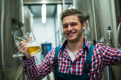 Brewer holding a glass of pint beer. Portrait of brewer holding a glass of pint beer stock photos