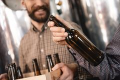 Brewer holds empty beer bottle in hand. Stages of brewing production. Process of beer manufacturing. stock images