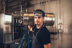 Brewer with keg at brewery factory. Portrait of male brewer with keg at brewery factory. Young man holding a metal beer container on shoulder at warehouse Royalty Free Stock Images