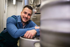 Brewer leaning on keg. Portrait of happy brewer leaning on keg at brewery Stock Photo