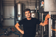 Brewer standing by beer filling machine at brewery factory Royalty Free Stock Photography