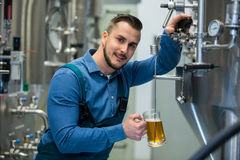 Brewer testing beer from tank. Portrait of happy brewer testing beer from tank at brewery Royalty Free Stock Images