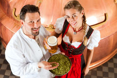 Brewer and woman with beer glass in brewery Royalty Free Stock Images