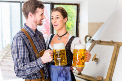 Brewer and woman toasting at beer brewery Royalty Free Stock Images