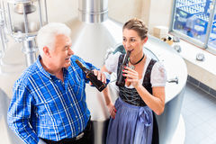 Brewer and woman toasting in beer brewery Royalty Free Stock Image