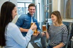 Brewers having beer at brewery. Happy brewers having beer at brewery Stock Images