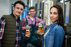 Brewers holding beer glasses at brewery factory Stock Photo