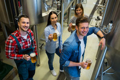 Brewers holding glass of beer standing at brewery Stock Photography