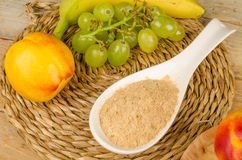Brewers yeast. A spoon full of brewers yeast surrounded by fresh fruit stock photo