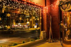 Brewery and bar at night with lights in downtown urban area. Night scene of urban area with brew kettles, bar and beer making items Stock Photo