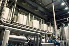 Brewery manufacturing factory. Stainless steel vats or tanks with pipes, brewing equipment, modern alcohol production technology. Toned stock photo