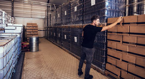 Brewery owner verifying the beer boxes in delivery storage area Royalty Free Stock Photo