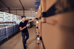 Brewery warehouse manager taking inventory. Young man taking the stock of packaged beer boxed in warehouse. Warehouse manager taking finished goods inventory at Stock Photography