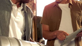 Brewery workers holding a keg and checking on a tablet stock footage