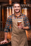Brewing the best beer. Happy young male brewer in apron holding glass with beer and smiling while standing in front of metal containers Stock Photos