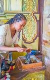Brewing coffee in Ethiopian ceremony. KIEV, UKRAINE - JUNE 4, 2017: Ethiopian Tigrayan girl - the master of ethnic coffee ceremony pours the coffee to jebena Royalty Free Stock Photo