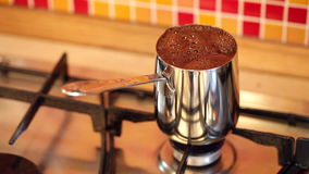 Brewing coffee in inox cezve on a gas stove stock footage