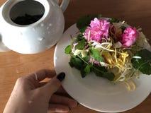 Brewing flower tea from fresh jasmine honeysuckle rose and lemon balm stock images