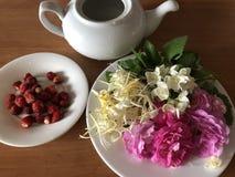 Brewing flower tea from fresh jasmine honeysuckle rose and lemon balm stock image