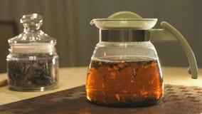 Brewing kipany tea in a glass teapot stock video