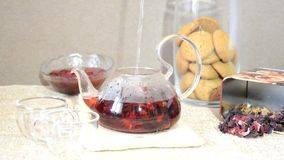 Brewing process of red tea/ Serving table for breakfast, red tea in teapot. tea leaves, hibiscus and two glass cups with. Brewing process of red tea. Serving stock video
