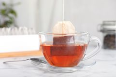 Brewing tea with bag in cup. On table stock images