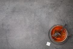 Brewing tea with bag in cup on table, top view. Space for text royalty free stock photo